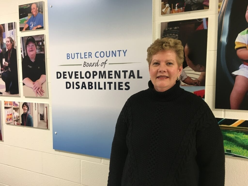 A woman stands in front of the Butler County Board of Developmental Disabilities logo. She smiles directly at the camera.