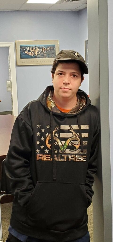 A man leans against a wall. He has a cap on and his hands in the pockets of his hoodie.