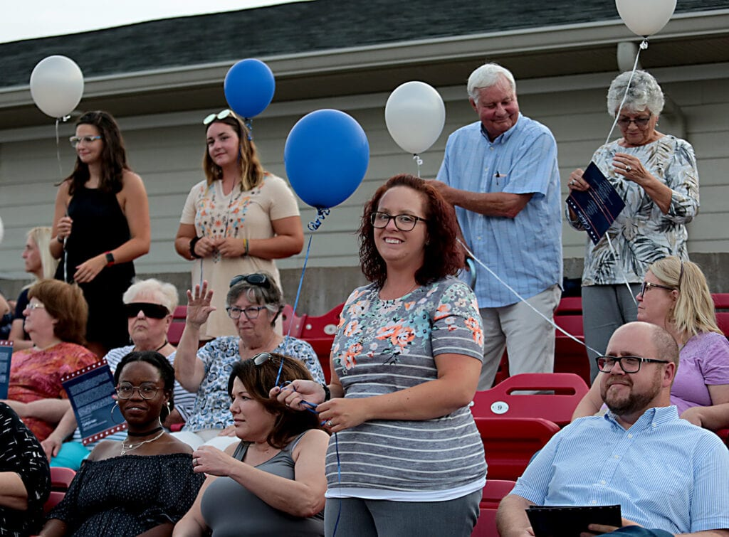 A woman stands holding a blue balloon. She is surrounded by other seated people.